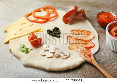 Fresh ingredients for pizza preparing on wooden table, close up