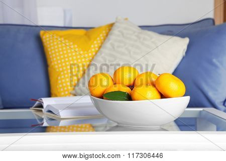 Bowl with fresh tangerines on table in living room, close up