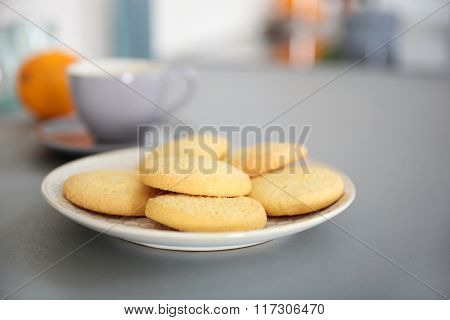 Cup of coffee and plate of cookies on the table against unfocused background