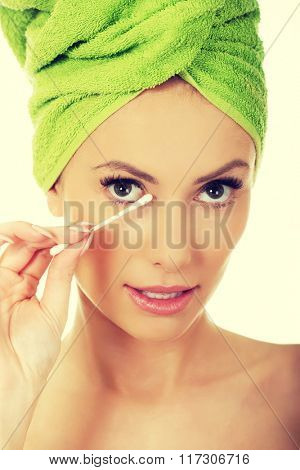 Woman removing make up with cotton bud.