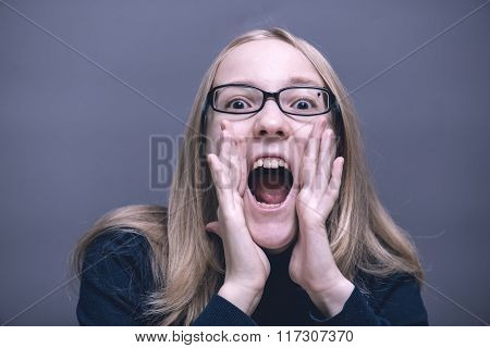 Portrait of a young girl on a gray background. Frightened shocked scared woman