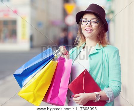 Young attractive happy shopper woman wearing hat and glasses holding shopping bags  walking in the city street