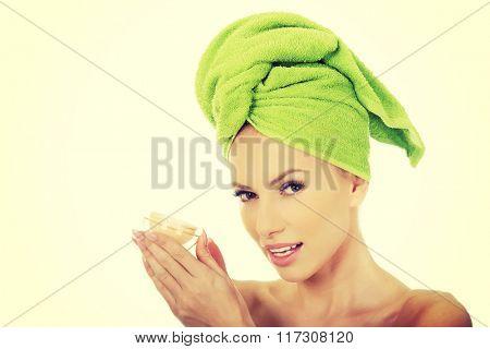 Woman holding a cream moisturizer.