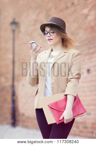 Young attractive student woman wearing hat and glasses holding a briefcase using a smart phone in the street. Technology internet communication and social media concept.