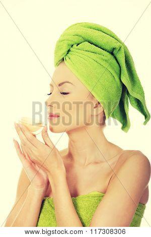 Woman smelling cream moisturizer.