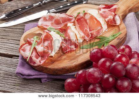 Prosciutto and mozzarella on cutting board over wooden table