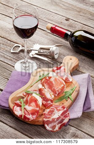 Prosciutto and mozzarella with red wine on wooden table