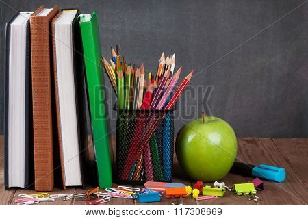 School and office supplies and apple on classroom table in front of blackboard. View with copy space