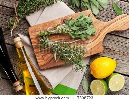 Fresh garden herbs and condiments on wooden table. Oregano, thyme, sage, rosemary. Top view