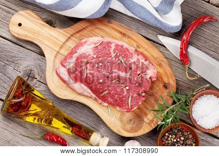 Raw beef steak with spices and herbs on wooden table. Top view