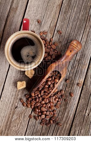 Coffee cup, beans and brown sugar on wooden table. Top view