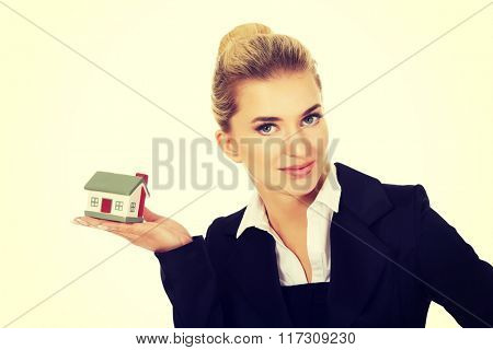 Happy businesswoman holding a house model