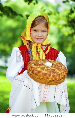 Little girl is dressed in the Russian national dress. She holds in his hands the fresh loaf. It is a custom to meet the guests.