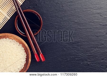 Japanese sushi chopsticks over soy sauce bowl and rice on black stone background. Top view with copy space. Toned