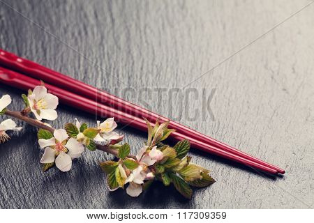 Japanese sushi chopsticks and sakura blossom on black stone background. Top view with copy space. Toned