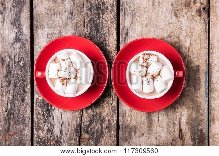 Two Red Cups Of Cocoa With Marshmallow On Table
