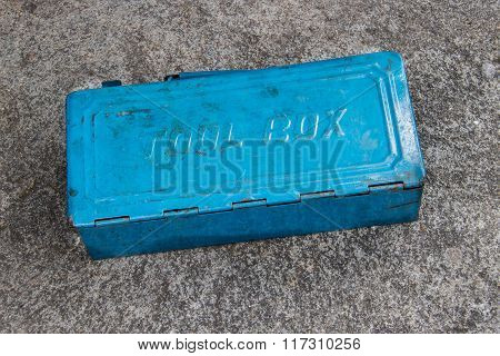 Blue metal tool box with many tools on concrete floor