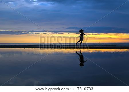 Silhouette of a happy lady jumping on the beach during a beautiful sunrise