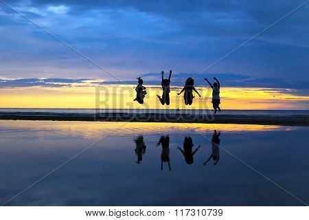 Silhouette of a happy four ladies jumping on the beach during a beautiful sunrise