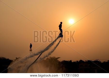 The new spectacular sport,Silhouette of two man showing the fly board in the river of Thailand