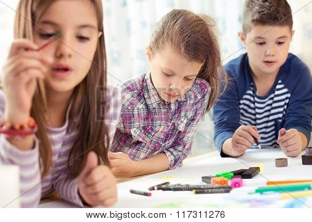 Child painting at easel in school