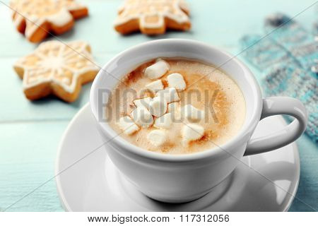Cup of hot cacao with marshmallow, cookies and warm gloves on blue table
