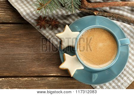Cup of coffee with star shaped biscuits and Christmas tree branch on napkin