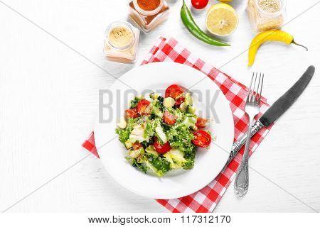Tasty salmon salad on light wooden background
