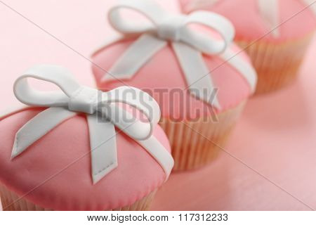 Tasty cupcakes with bow on color wooden background