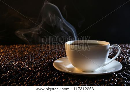 Cup of hot coffee among coffee beans on dark background