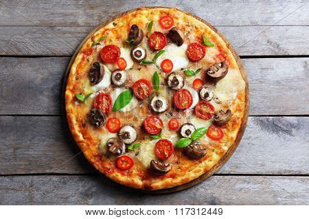 Tasty fresh pizza decorated with mushrooms and tomatoes on wooden background, close up