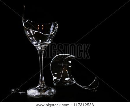 Broken wine glass on black background