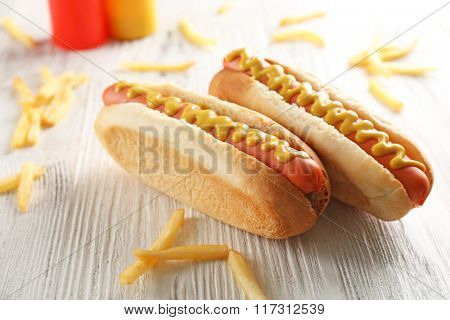 Hot dogs and fried potatoes on wooden background