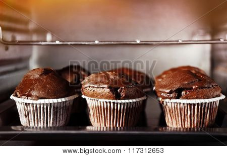 Chocolate cup-cakes in oven, close up