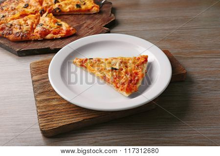 Slice of tasty pizza on white plate on wooden table, close up