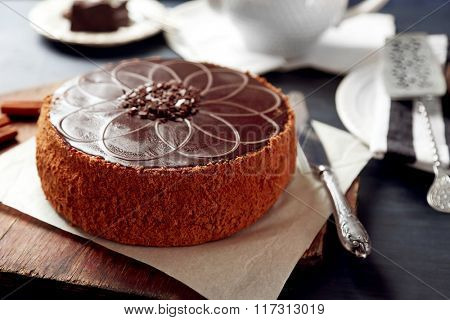 Tasty chocolate cake on color wooden background