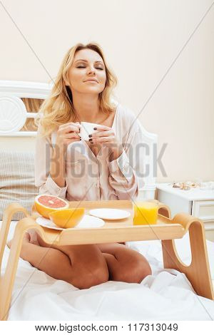 young beauty blond woman having breakfast in bed early sunny morning, princess house interior room,