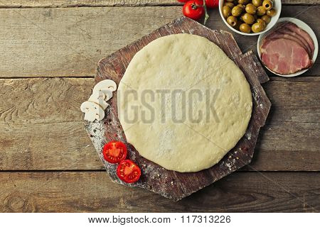 Fresh dough prepared for pizza with tomatoes and sliced mushrooms on a wooden board, close up