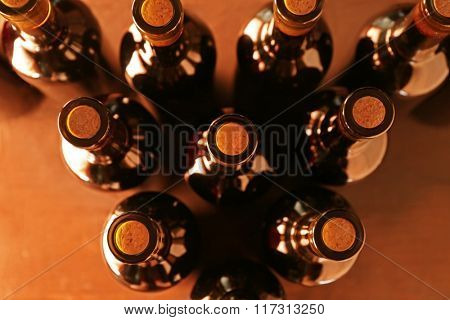Stacks of wine bottles on wooden background, upside view. Close up