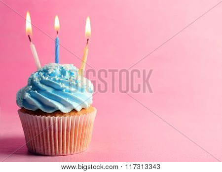 Tasty cupcake decorated with candle on pink background