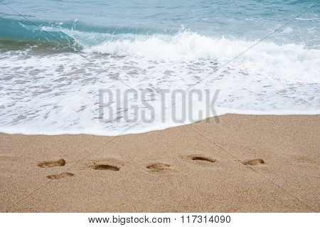 Sea, Sand And Footprints In The Sand..