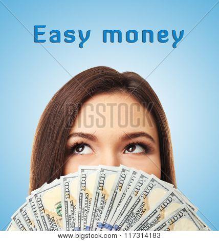 Woman holding money on blue background
