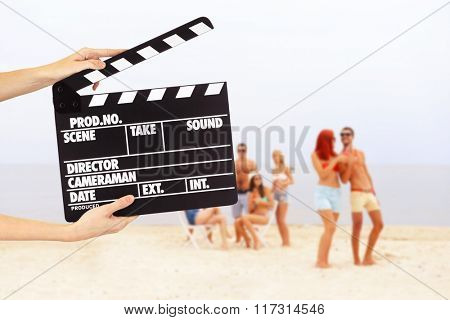 Operator holding clapperboard during the production of the film outdoor