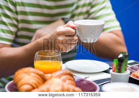 Man have breakfast with croissants, coffee and fresh orange juice