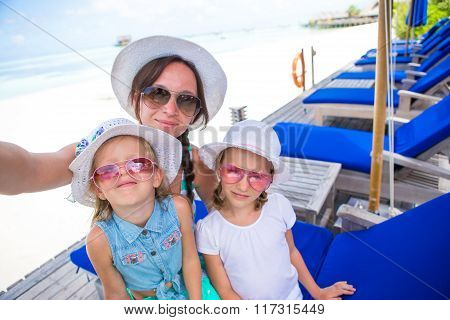 Mother and little girls taking self portrait at tropical vacation