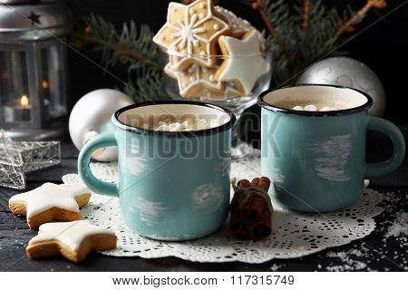 Two mugs of hot cacao with marshmallow and cookies on black table