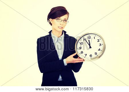 Business woman holding clock in hands.