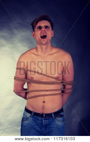 Tortured man tied with a rope.