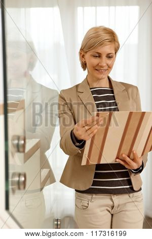 Blonde businesswoman looking at folder holding in hands, standing by stairs.