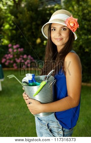 Outdoor portrait of attractive gardening girl, holding bucket, smiling, looking at camera.